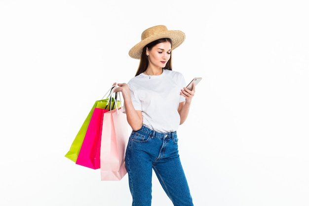 Porträt des einkaufens der herrlichen frau unter verwendung ihres smartphones lokalisiert auf weißer wand Kostenlose Fotos