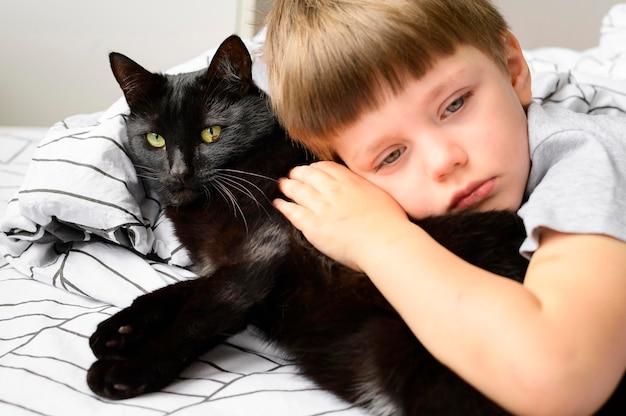 Porträt des entzückenden jungen, der seine katze umarmt Kostenlose Fotos