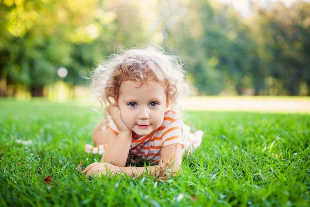 Porträt des entzückenden kleinen lockenmädchens, das auf gras liegt und oben ihr gesicht am sommergrünpark stützt Premium Fotos