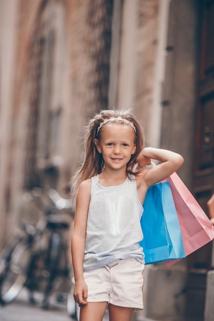 Porträt des entzückenden kleinen mädchens, das draußen mit einkaufstaschen in europäische stadt geht. Premium Fotos