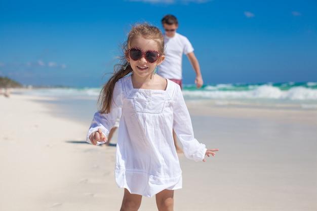 Porträt des entzückenden mädchens und seines vaters mit kleiner schwester am tropischen strand Premium Fotos