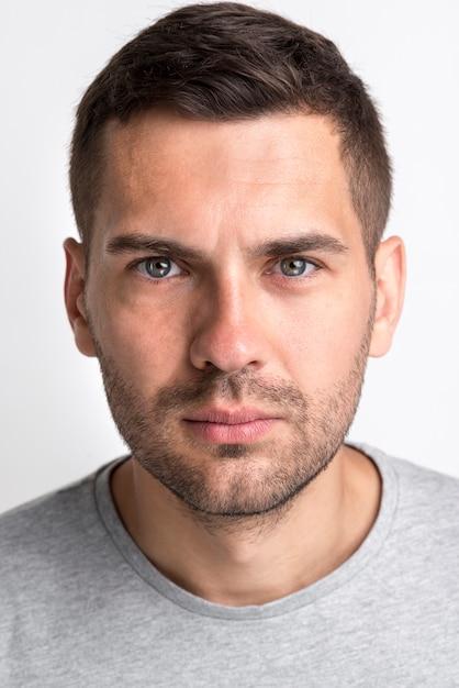 Porträt des ernsten gutaussehenden mannes kamera gegen weißen hintergrund betrachtend Kostenlose Fotos