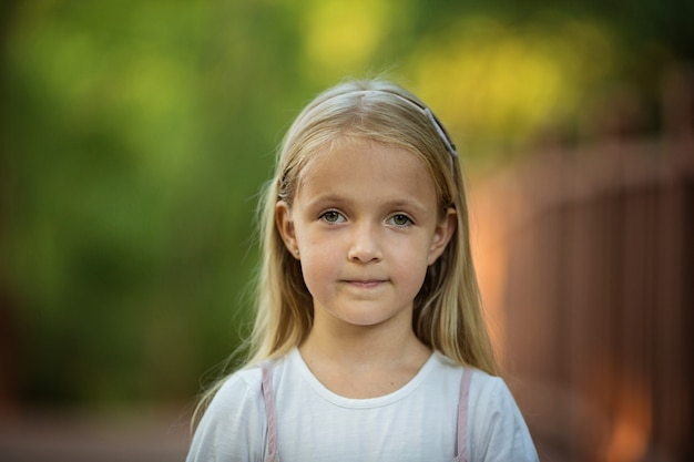 Porträt des ernsten kleinen mädchens mit dem blonden haar im freien Premium Fotos