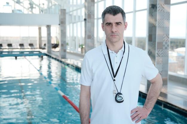 Porträt des ernsthaften schönen reifen schwimmtrainers im weißen poloshirt, das am pool steht Premium Fotos