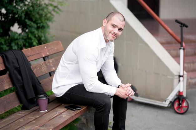 Porträt des erwachsenen mannes, der auf einer bank sitzt Kostenlose Fotos