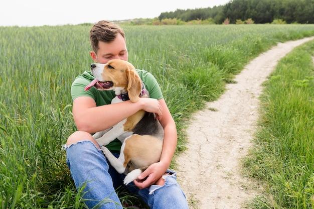 Porträt des erwachsenen mannes, der natur mit hund genießt Kostenlose Fotos