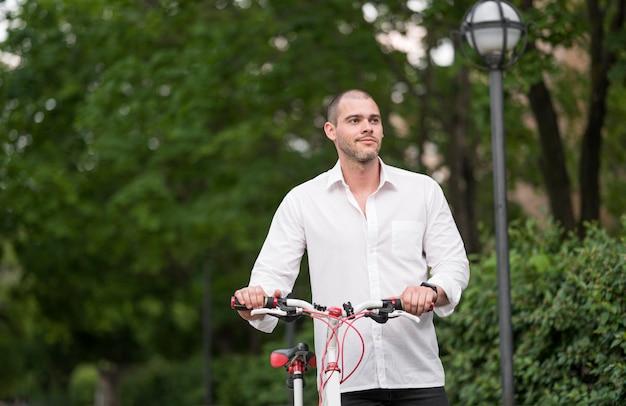 Porträt des erwachsenen mannes mit fahrrad im freien Kostenlose Fotos
