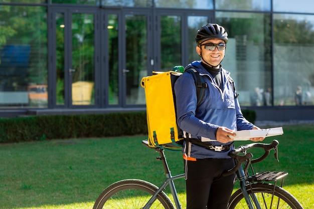 Porträt des fahrradkuriers mit gelber tasche und fahrrad Premium Fotos