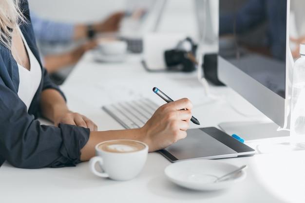 Porträt des freiberuflichen webdesigners, der kaffee am arbeitsplatz trinkt und stift hält. leicht gebräunte dame im schwarzen hemd mit tablette in ihrem büro, sitzend vor computer. Kostenlose Fotos