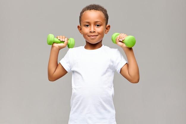 Porträt des fröhlichen afroamerikanischen jungen mit den dünnen armen, die glücklich lächeln, während sie im fitnessstudio mit zwei hanteln trainieren, um starken gesunden sportlichen körper aufzubauen. fitness und kinder Kostenlose Fotos
