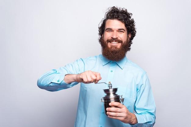 Porträt des fröhlichen bärtigen mannes im lässigen halten der manuellen kaffeemühle und des lächelns. Premium Fotos