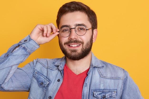 Porträt des fröhlichen magnetischen bärtigen glücklichen jungen mannes, der direkt aufrichtig lächelnd schaut und angenehmen gesichtsausdruck hat Kostenlose Fotos