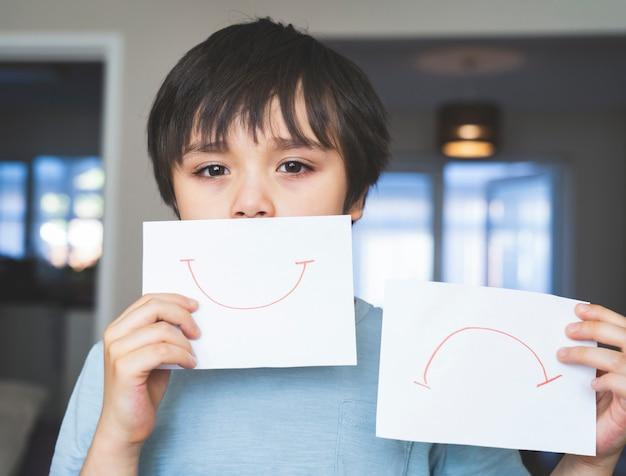 Porträt des gelangweilten kindes mit dem traurigen gesicht, das weißes papier mit lächeln und traurig hält, kinderjunge, der geboren wird, bleibt während der selbstisolierung, quarantäne zu hause. coronavirus-ausbruch und grippe-covid-epidemie Premium Fotos