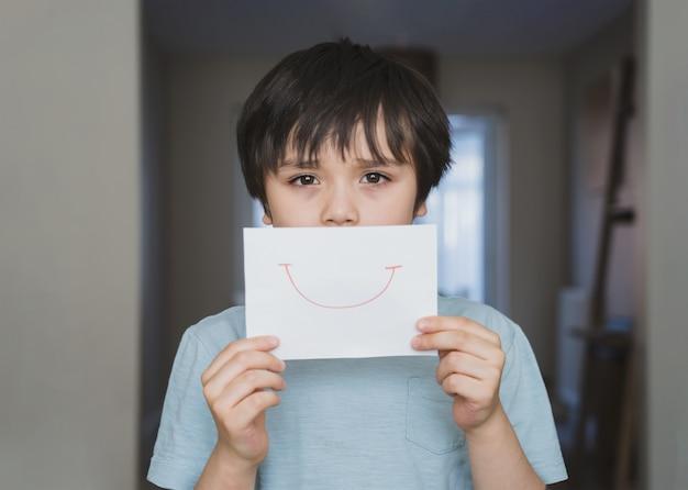 Porträt des gelangweilten kindes mit traurigem gesicht, das weißes papier mit lächeln hält, kinderjunge, der geboren wird, bleibt während der selbstisolation zu hause Premium Fotos