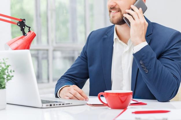 Porträt des geschäftsmannes, der am telefon im büro spricht Kostenlose Fotos