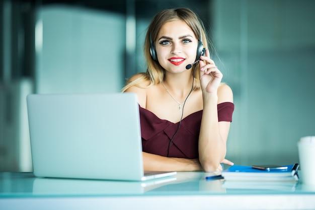 Porträt des glücklich lächelnden weiblichen kundenbetreuungs-telefonbetreibers am arbeitsplatz. Kostenlose Fotos