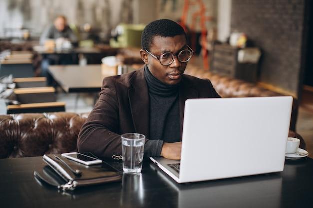 Porträt des glücklichen afrikanischen geschäftsmannes unter verwendung des telefons beim arbeiten an laptop in einem restaurant. Premium Fotos