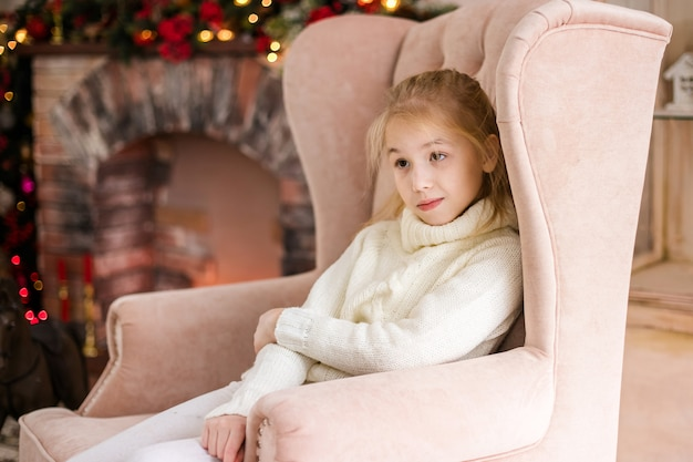 Porträt des glücklichen blonden kindermädchens in der weißen strickjacke, die auf dem boden nahe dem weihnachtsbaum stationiert Premium Fotos