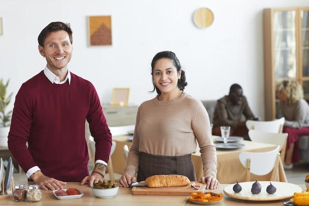 Porträt des glücklichen erwachsenen paares und des lächelns beim kochen für die dinnerparty drinnen, Premium Fotos