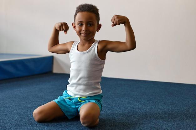 Porträt des glücklichen fröhlichen dunkelhäutigen jungen mit der kurzen afro-frisur, die am fitnesscenter trainiert Kostenlose Fotos