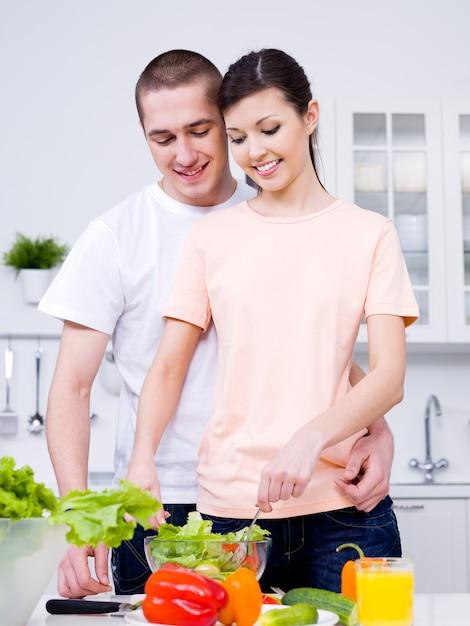 Porträt des glücklichen fröhlichen jungen paares, das zusammen frühstück macht Kostenlose Fotos