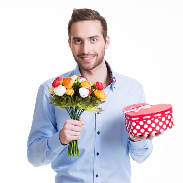 Porträt des glücklichen gutaussehenden mannes mit blumen und einem geschenk - lokalisiert auf weiß. Kostenlose Fotos