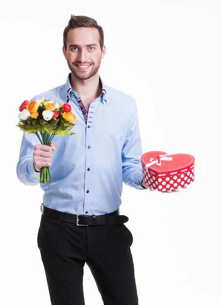 Porträt des glücklichen gutaussehenden mannes mit blumen und einem geschenk - lokalisiert auf weiß Kostenlose Fotos