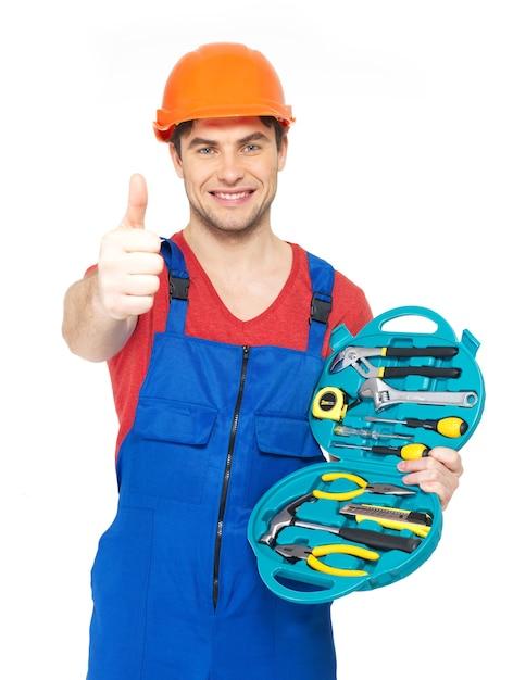 Porträt des glücklichen handwerkers mit werkzeugen, die daumen auf zeichen lokalisiert auf weiß zeigen Kostenlose Fotos
