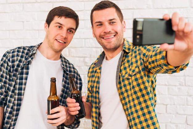 Porträt des glücklichen jungen mannes, der in der hand die bierflasche nimmt selfie mit seinen freunden auf smartphone hält Kostenlose Fotos
