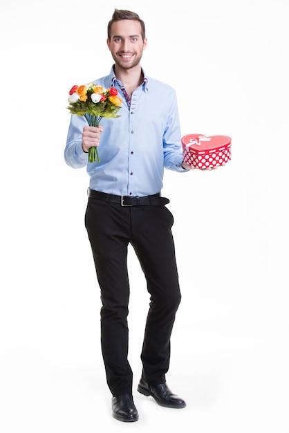 Porträt des glücklichen jungen mannes mit blumen und einem geschenk - lokalisiert auf weiß. Kostenlose Fotos