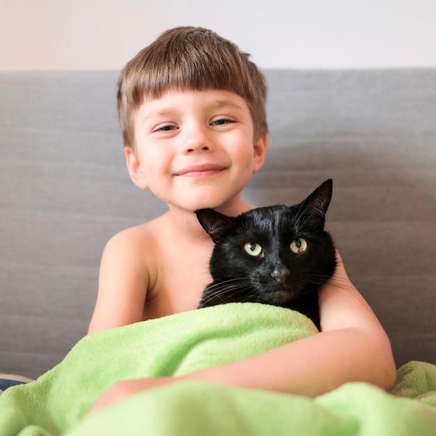 Porträt des glücklichen jungen mit seiner katze Kostenlose Fotos