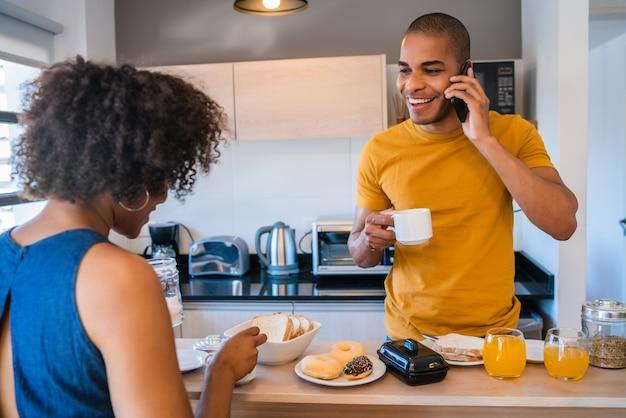Porträt des glücklichen jungen paares, das zusammen zu hause frühstückt Premium Fotos
