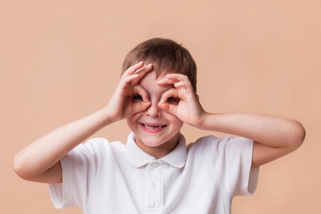 Porträt des glücklichen jungen schauend durch finger als ferngläser Kostenlose Fotos