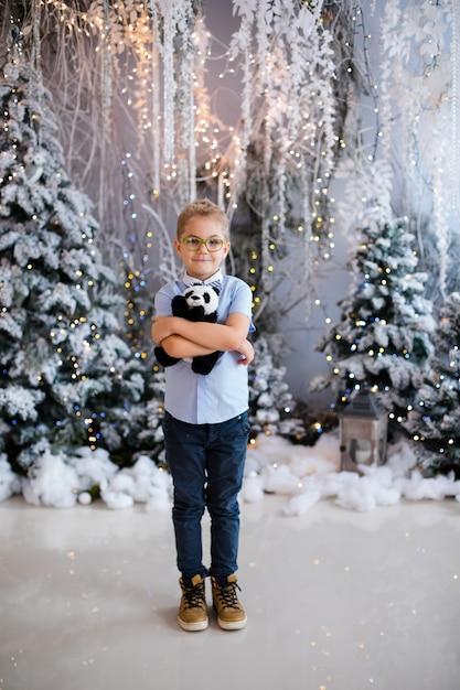 Porträt des glücklichen kinderjungen mit den großen gläsern, die spielzeug halten, tragen innenstudio Premium Fotos