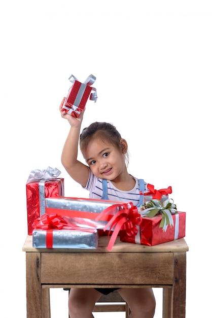 Porträt des glücklichen kleinen asiatischen mädchens mit vielen geschenkboxen lokalisiert auf weiß Premium Fotos