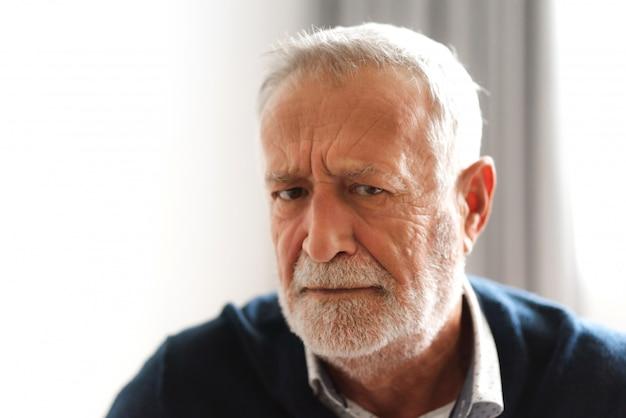 Porträt des glücklichen lächelnden älteren mannes, der kamera betrachtet Premium Fotos