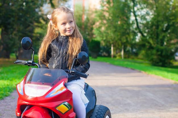 Porträt des glücklichen little rock-mädchens in der lederjacke, die auf ihrem spielzeugmotorrad sitzt Premium Fotos