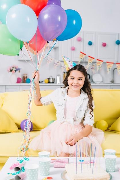 Porträt des glücklichen mädchens sitzend auf dem sofa, das bunte ballone hält Kostenlose Fotos