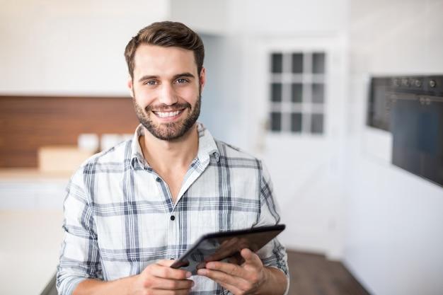 Porträt des glücklichen mannes, der digitale tablette verwendet Premium Fotos