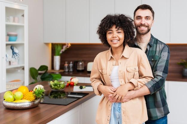 Porträt des glücklichen paars sitzend in der küche Premium Fotos