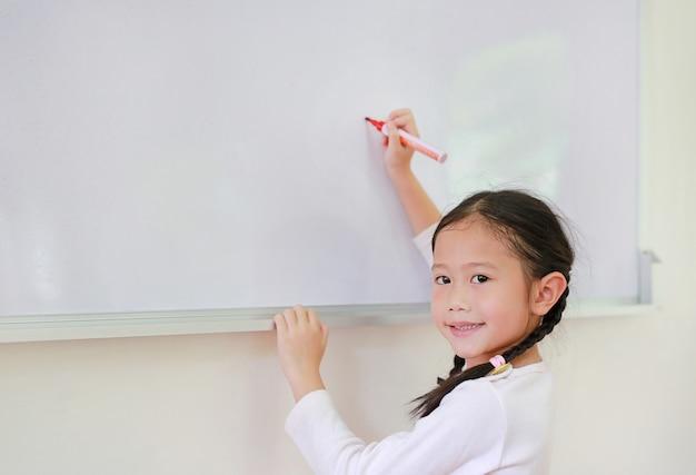 Porträt des glücklichen schulmädchenschreibens etwas auf whiteboard mit einer markierung. Premium Fotos