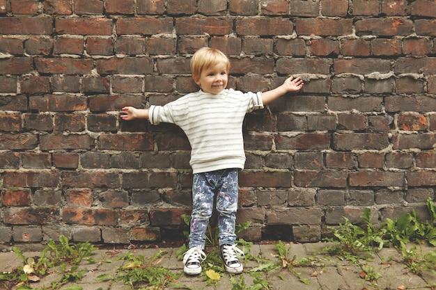 Porträt des glücklichen sorglosen kleinen jungen. winziges kind, das nahe ziegelmauer steht und arme draußen streckt. er trägt ein gestreiftes t-shirt, lässige jeans mit bunten flecken und grunge-gummischuhe. löwenzahn wächst herum. Kostenlose Fotos