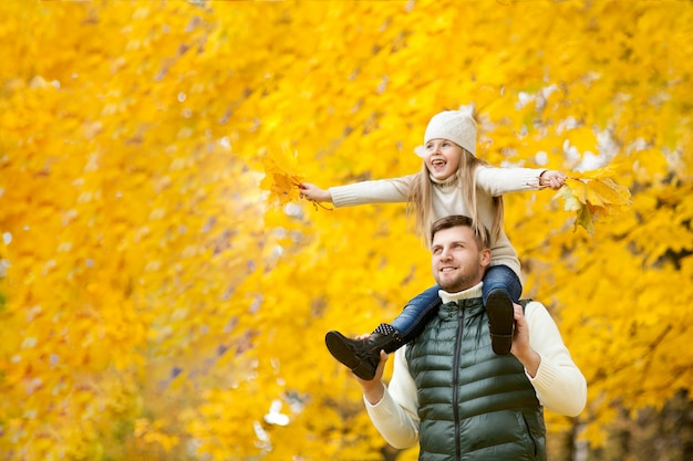 Porträt des glücklichen vaters ihre tochter auf schultern halten, mit blättern im handson den herbstpark Premium Fotos