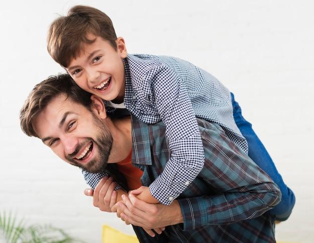 Porträt des glücklichen vaters umfasst von seinem sohn Kostenlose Fotos