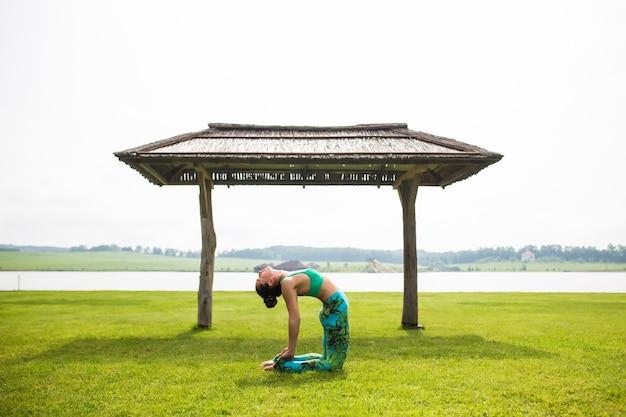 Porträt des glücks junge frau, die yoga im freien praktiziert Kostenlose Fotos
