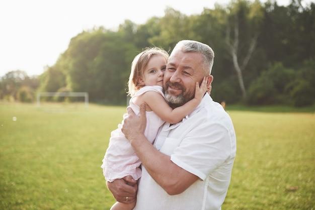 Porträt des großvaters mit der enkelin, zusammen entspannend im park Premium Fotos
