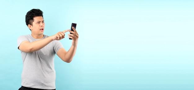 Porträt des gutaussehenden asiatischen mannes, der schock und überrascht ist, nachdem er nachricht von smarrtphone gelesen hat, lokalisiert auf blauer wand. Premium Fotos