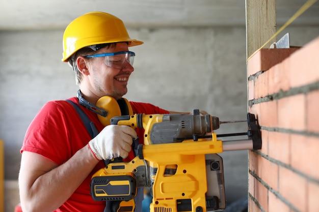 Porträt des handwerkerbauers unter verwendung des perforators, um loch in konstruierte wand zu bohren. reparatur oder reparatur, industriearbeiter mit instrument zur auftragserfüllung Premium Fotos