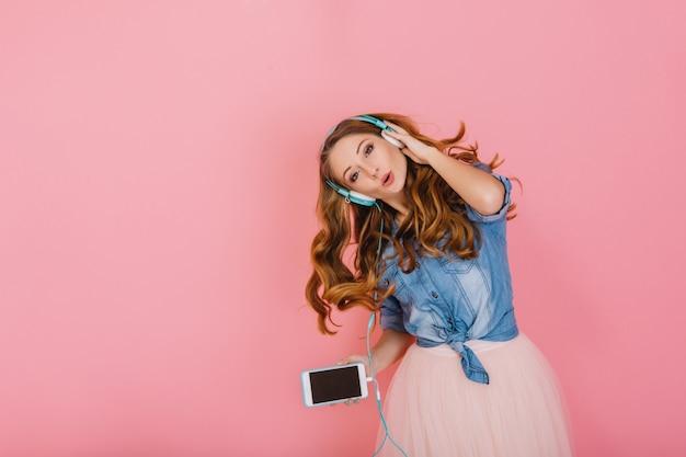 Porträt des herrlichen glücklichen langhaarigen mädchens in den kopfhörern, die lieblingslied singen, isoliert auf rosa hintergrund. attraktive lockige junge frau im jeanshemd mit smartphone, das tanzt und musik genießt Kostenlose Fotos