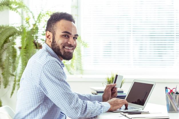Porträt des hübschen afrikanischen schwarzen jungen geschäftsmannes, der an laptop im büro arbeitet Premium Fotos